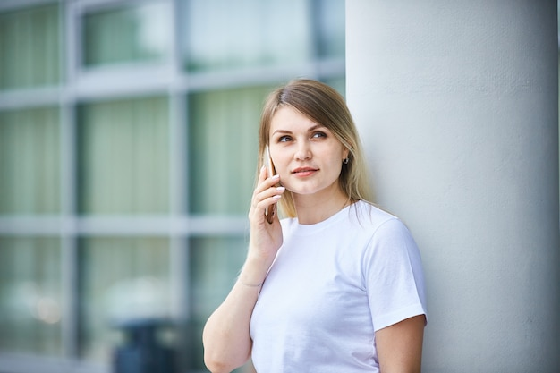 Chica europea con el pelo lacio hablando por teléfono.