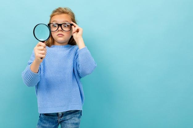 Chica europea sorprendida en gafas mira a través de una lupa en azul claro con copyspace