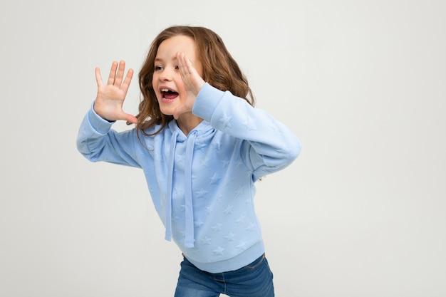 Chica europea en una sudadera con capucha azul grita mientras toma las manos en la boca en una pared de luz
