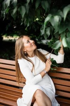 Chica europea se ve, en el follaje de un arbusto o árbol.