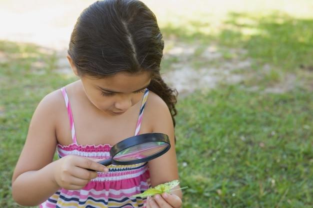 Chica examinando una hoja con lupa en el parque