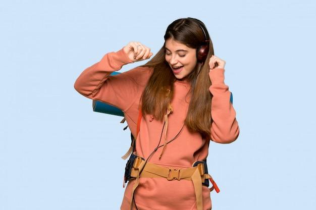 Chica excursionista escuchando música con auriculares y bailando en azul