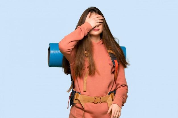 Chica excursionista que cubre los ojos con las manos. no quiero ver algo en azul