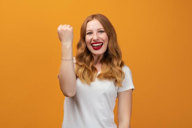 Chica exitosa con largo cabello rubio ondulado, vestida con camiseta blanca sonriendo felizmente, celebrando noticias increíbles, haciendo gesto de ganador, fondo amarillo de pie