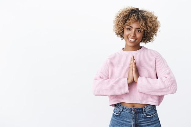 Chica expresando gracias de manera asiática. retrato de encantador feliz afroamericano con piercing y cabello rubio sosteniendo las palmas juntas sobre el cuerpo en gesto de rezar o namaste sonriendo amigable y relajado
