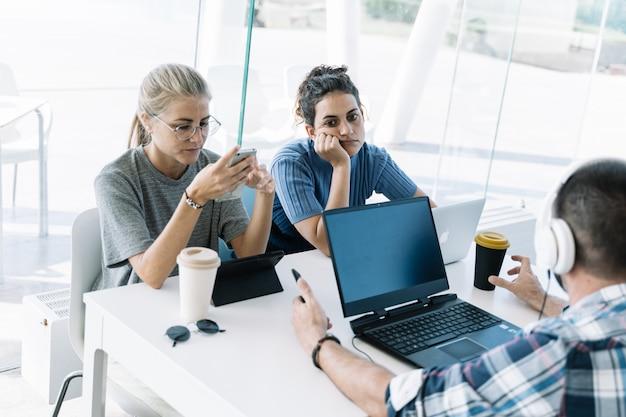 Chica con una expresión aburrida sentada en una mesa con otras personas trabajando