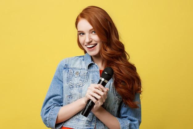 Chica expresiva cantando con un micrófono, fondo amarillo brillante aislado.