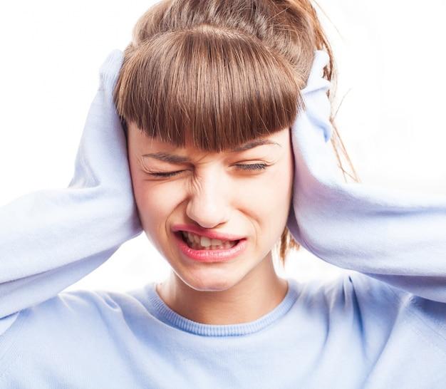 Chica expresiva cubriendo sus orejas