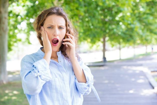 Chica extremadamente sorprendida exasperada con conversación telefónica