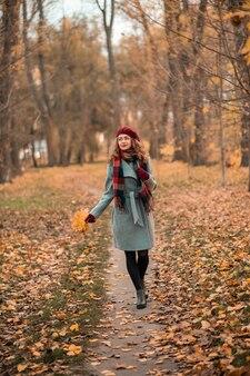 Chica en el fabuloso fondo del parque con hojas de otoño naranja en las manos caminando por la carretera