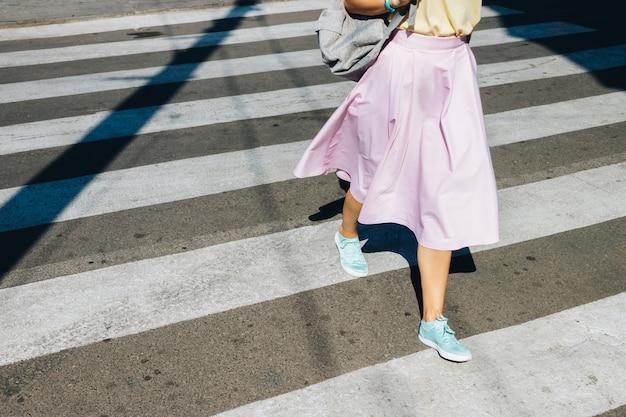 Chica en una falda rosa y zapatillas de deporte cruzando la calle en el verano