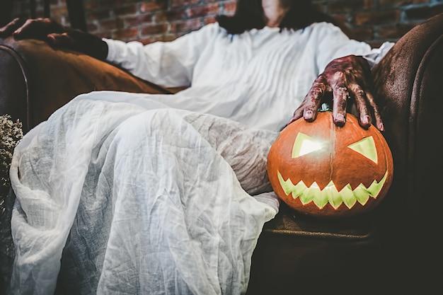 Chica fantasma en la sangre con vestido blanco sosteniendo la calabaza de halloween y sentado en la vieja