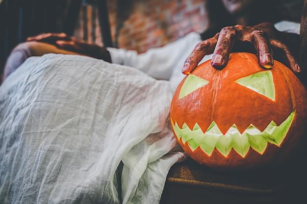Chica fantasma en la sangre con vestido blanco sosteniendo la calabaza de halloween