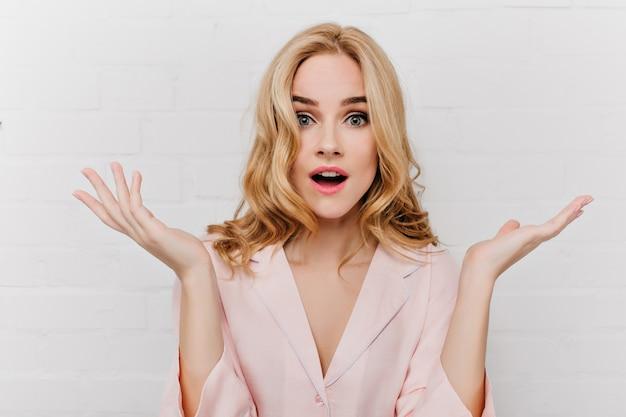Chica fascinante con grandes ojos azules expresando asombro y agitando las manos aisladas en la pared blanca. hermosa mujer con peinado rizado viste pijama rosa posando con cara de sorpresa.