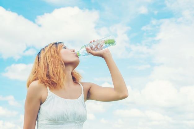 Chica feliz bebiendo agua con el cielo de fondo