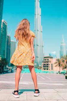 Chica feliz caminando en dubai con rascacielos en el fondo.