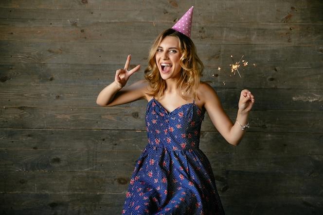 Chica feliz celebrando la fiesta de cumpleaños, mostrando el signo de la paz, sostiene la luz de bengala