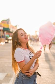 Chica feliz comiendo algodón de azúcar
