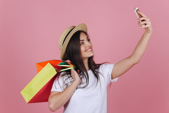 Chica feliz con coloridos bolsos de compras toma selfie en su teléfono