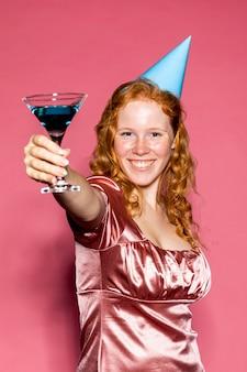 Chica feliz cumpleaños animando con un cóctel