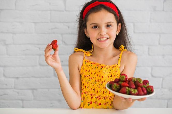 Chica feliz de pie contra la pared de ladrillo blanco con fresas rojas