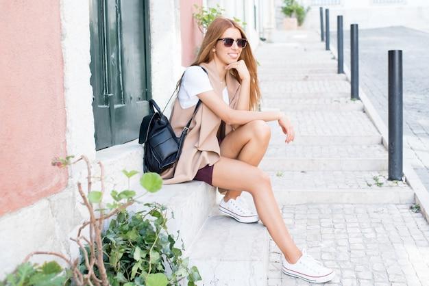Chica feliz disfrutando del buen tiempo en la ciudad