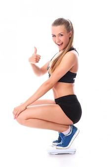 Chica feliz fitness en la balanza con el pulgar arriba