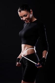 Chica feliz fitness midiendo su cintura