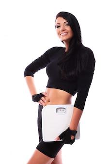 Chica feliz fitness sosteniendo escalas