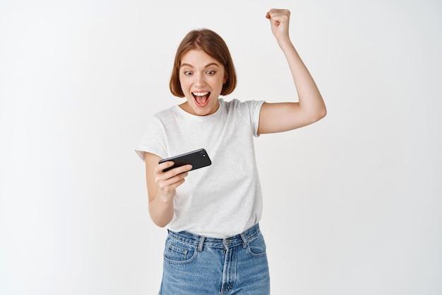 Chica feliz ganando videojuegos, levantando la mano y mirando el teléfono inteligente emocionado, celebrando la victoria en la aplicación móvil, pared blanca