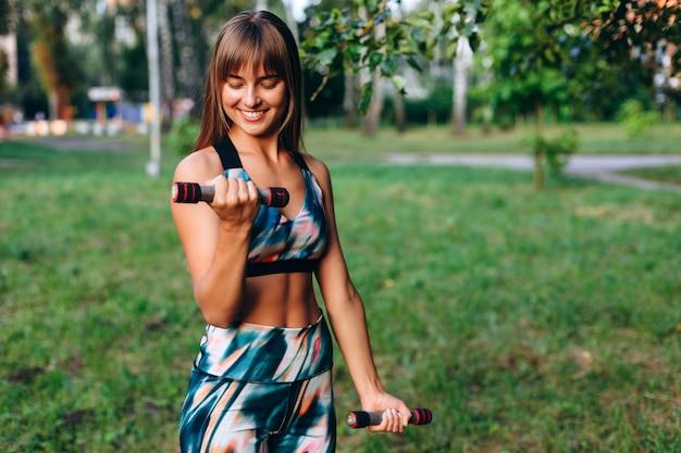 Chica feliz haciendo ejercicio con pesas al aire libre