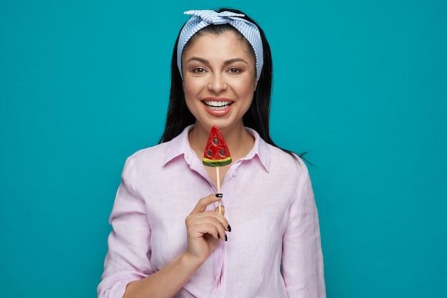 Chica feliz posando con piruleta de sandía.