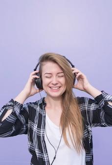 Chica feliz en la ropa casual escucha música en boquillas con los ojos cerrados sobre un fondo morado. el estudiante está escuchando música aislada sobre un fondo morado. copyspace