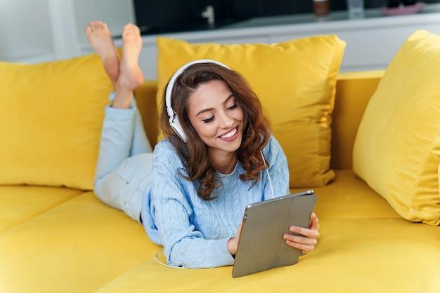 Chica feliz satisfecha usando tableta mientras está acostado en el cómodo sofá amarillo y disfruta de agradables melodías con auriculares.