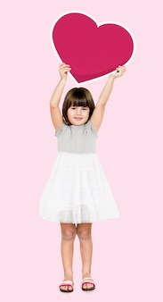 Chica feliz sosteniendo un icono de corazón