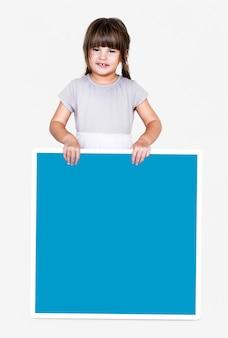 Chica feliz sosteniendo un tablero cuadrado vacío