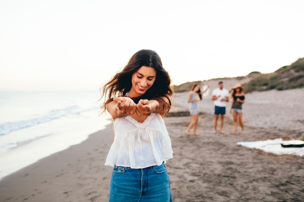 Chica feliz con sus amigos en la playa