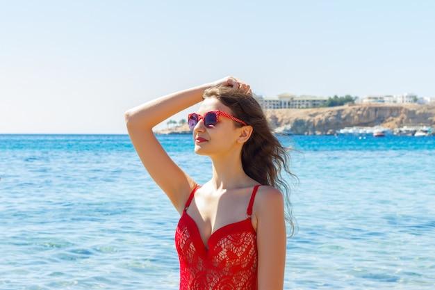 Chica feliz en traje de baño rojo relajante y posando en la playa