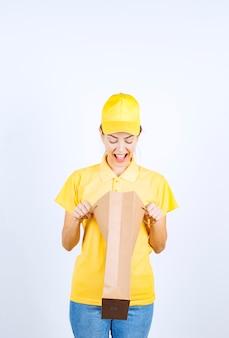 Chica femenina en uniforme amarillo abriendo y comprobando la bolsa de compras entregada.