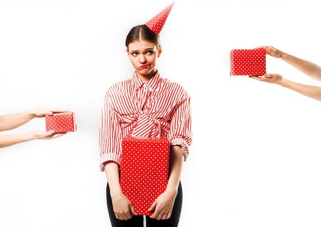 Chica en una fiesta en una camisa a rayas rojas con regalos en blanco