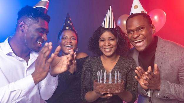 Chica de la fiesta de cumpleaños feliz con pastel y amigos