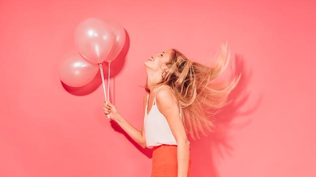 Chica fiestera posando con globos