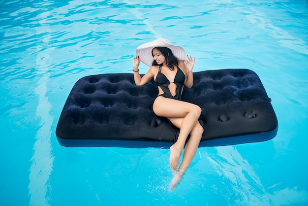 Chica con figura perfecta tumbada en colchón en piscina