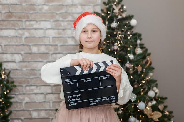 Chica filmando una película navideña en la sala de estar festiva