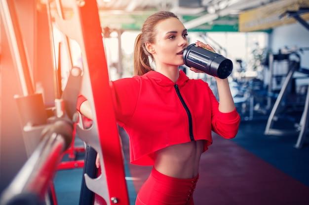 Chica fitness con agitador posando en el gimnasio