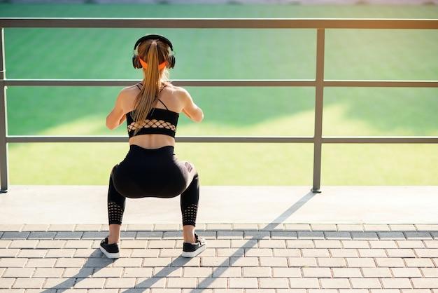 Chica fitness con auriculares que hace ejercicios de sentadillas con una banda de botín de tela durante su entrenamiento deportivo en un campo deportivo especial