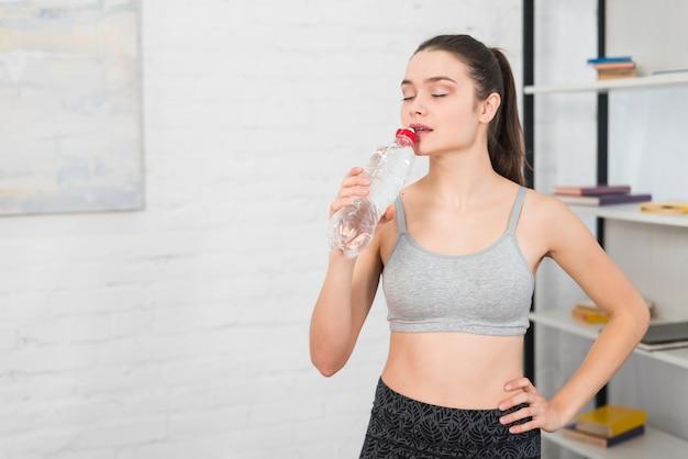 Chica fitness bebiendo agua