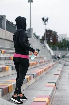 Chica fitness con botella de agua en la mano