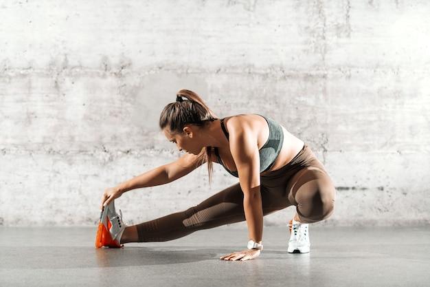 Chica fitness caucásica con cola de caballo y en ropa deportiva estirando la pierna delante de la pared gris.