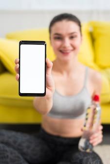 Chica fitness enseñando móvil